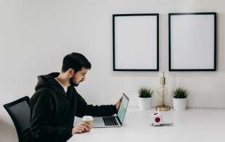 Man using Macbook laptop on white desk